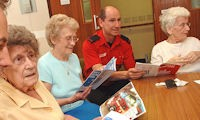 Older people sitting at a table with fire safety officers