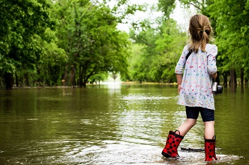 Young girl in park wearng wellies while standing in flood water