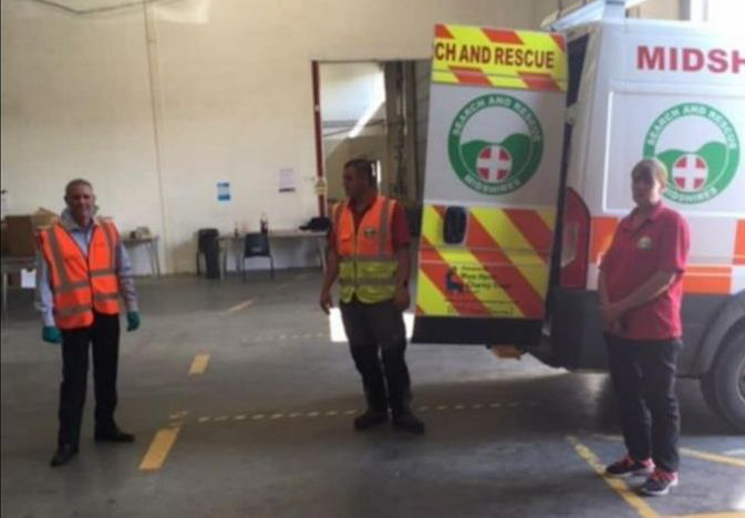 Staff standing by van at warehouse