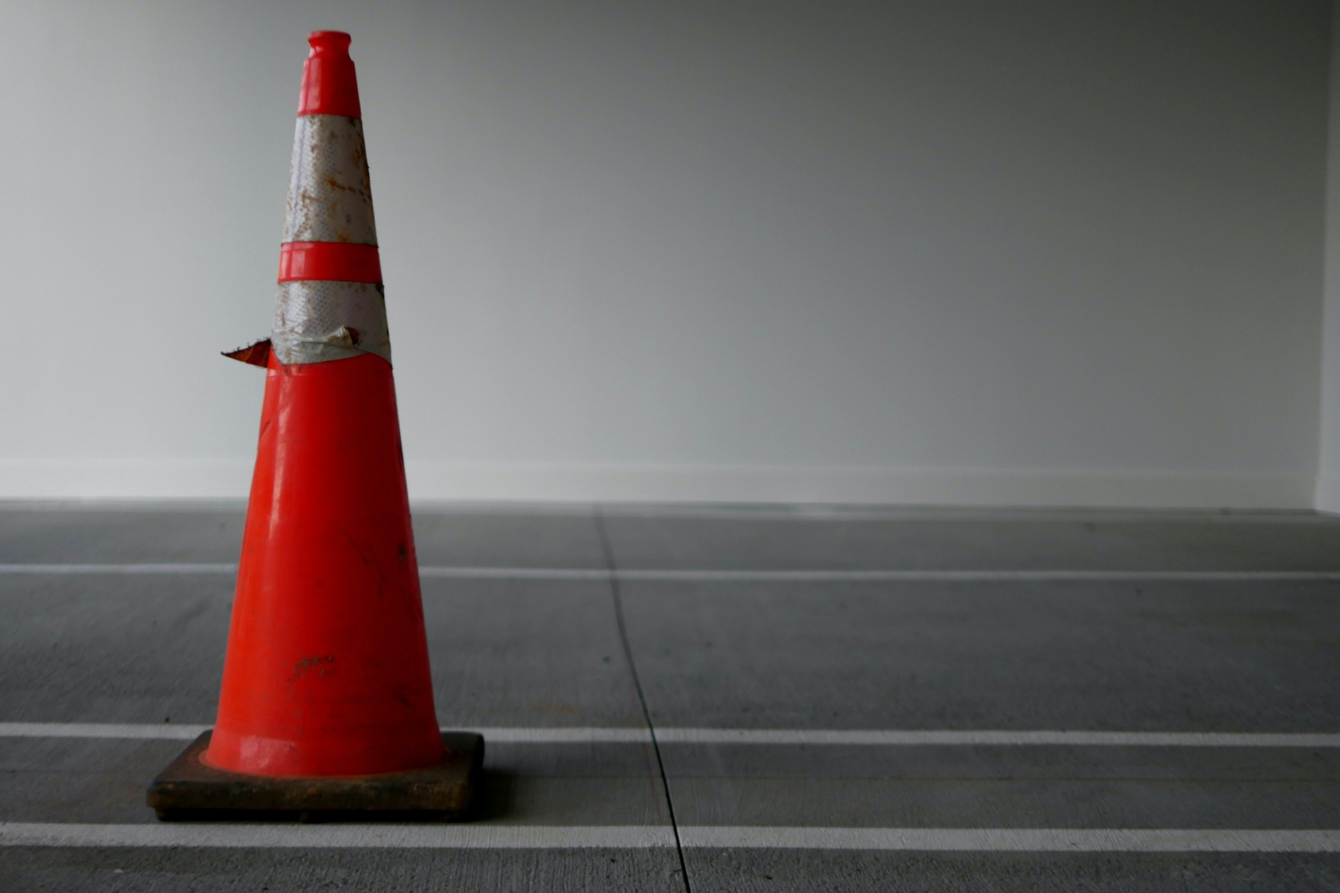 An orange and silver safety cone on road